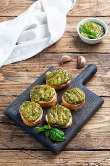 Kanapki z sosem pesto, świeżymi liśćmi bazylii i czosnkiem. pyszna zdrowa przekąska. drewniane rustykalne tło. kopiuj przestrzeń