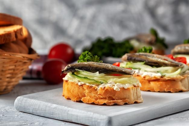 Kanapki z szprotkami na tostowych kromkach chleba. kanapka ze szprotem wędzonym - ryba, świeży ogórek i pomidor.