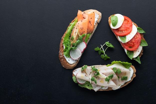 Kanapki z szynką, rzodkiewką, sałatką romano, młodą bazylią, serem mascarpone, sałatką caprese na czarnej ścianie.