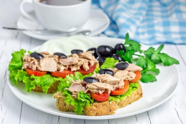 Kanapki z tuńczykiem na białym talerzu i kawa