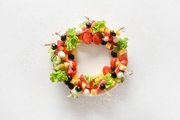 Kanapki z warzywami, oliwą, salami, przekąskami z sera mozzarella jako wieniec na przyjęcie świąteczne.