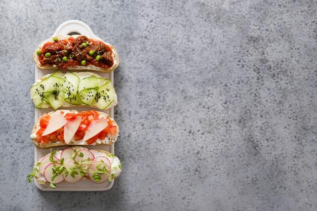 Kanapki z warzywami, rzodkiewkami, pomidorami, ogórkami i mikrogreenami na szaro. widok z góry.