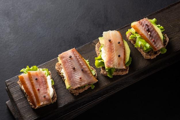 Kanapki z wędzoną rybą na desce na ciemnym tle