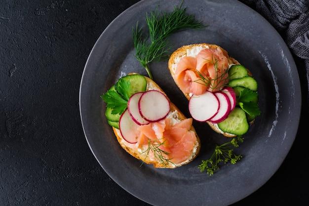 Kanapki z wędzonym różowym łososiem, rzodkiewką, ogórkiem i serem śmietankowym na szarym talerzu ceramicznym i tekstylnej powierzchni