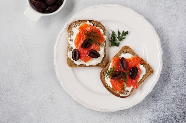 Kanapki z wędzonymi różowymi oliwkami łososia, kalamata, mikrogreenami i serem śmietankowym na szarym talerzu ceramicznym i modnym tle betonowym. tradycyjne skandynawskie tosty. widok z góry.