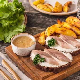 Kanapki ze śledziem i pieczony ziemniak. zbliżenie
