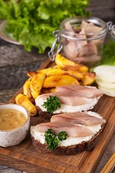 Kanapki ze śledziem i pieczonym ziemniakiem na desce.