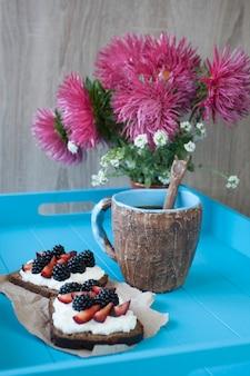 Kanapki ze słodkim serem i jagodami, filiżanka kawy w niebieskim drewnianym stole