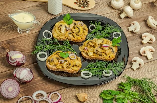 Kanapki ze smażonymi pieczarkami na czarnym talerzu na ciemnym tle drewniane ze składnikami i sosem.