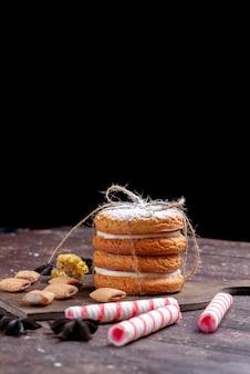 Kanapkowe ciasteczka ze śmietaną wraz z cukierkami w sztyfcie na brązowym biurku
