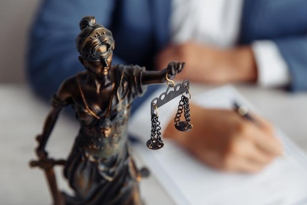 Kancelaria prawnika statua sprawiedliwości z wagą i prawnikiem