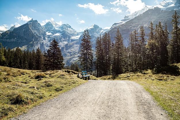 Kandersteg szwajcaria - ławka w drodze do oeschinensee z widokiem na rothorn, bluemlisalphorn, oeschinenhorn, fruendenhorn i doldenhorn