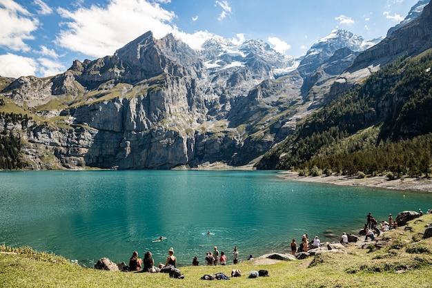 Kandersteg szwajcaria - ludzie cieszący się słońcem nad oeschinesnsee z widokiem na rothorn, bluemlisalphorn, oechinenhorn, fruendenhorn