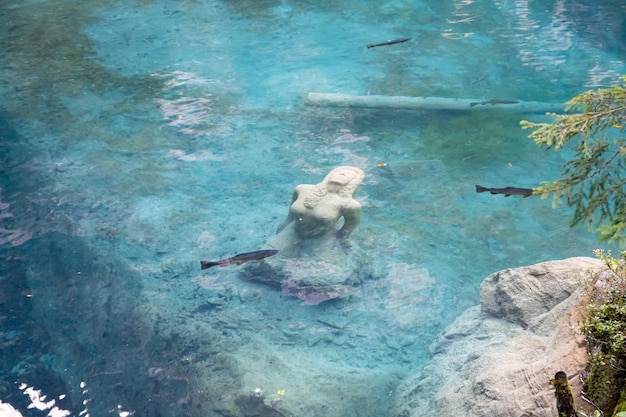 Kandersteg szwajcaria - widok na blausee z posągiem kobiety w jeziorze, raphaela fuchsa