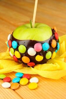 Kandyzowane jabłko na patyku na drewnianym stole