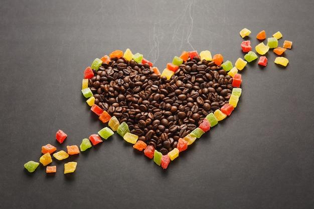 Kandyzowane owoce w formie serca ze strzałką, brązowe ziarna kawy na białym na czarnym tle do projektowania. karta świętego walentego na 14 lutego, koncepcja wakacje. skopiuj miejsce na reklamę.