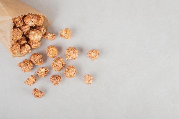Kandyzowany popcorn wysypujący się z opakowania papieru na marmurowym tle.