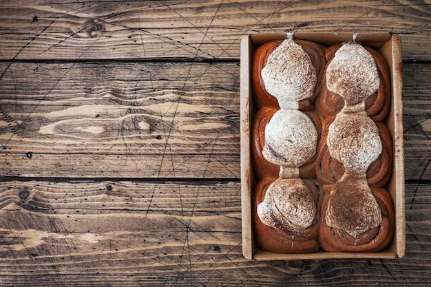 Kanelbulle bułeczki cynamonowe z kremem na rustykalnym drewnianym stole. domowe świeże wypieki. widok z góry, kopia przestrzeń.