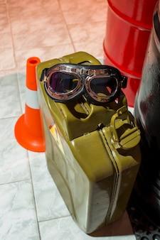 Kanister benzyny z okularami przeciwsłonecznymi w pobliżu beczek