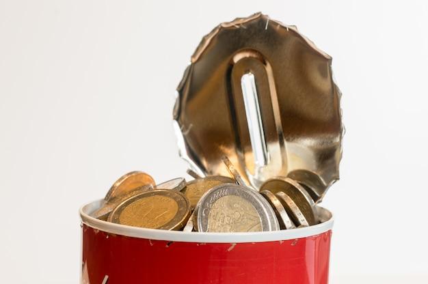 Kanister cynowy, otwarty, z licznymi monetami euro, opadający wokół niego. pojęcie wydawania oszczędności.