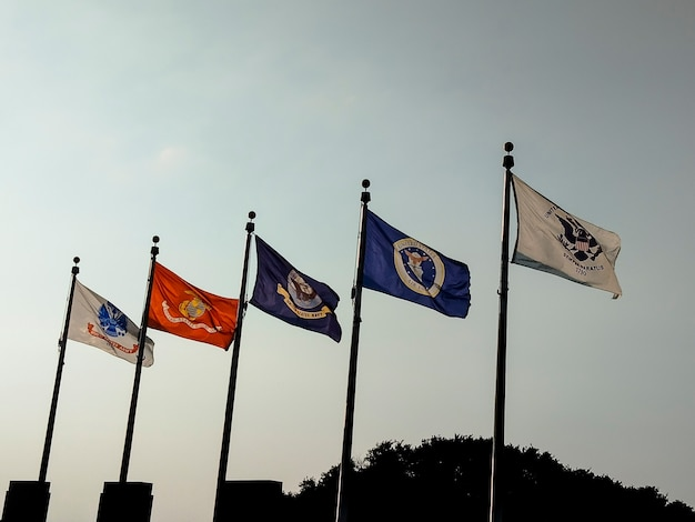 Kansas city, kansas. flagi sił zbrojnych powiewające pod pomnikiem kapłanów, którzy służyli w wojsku.