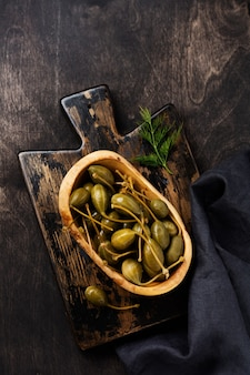 Kapary w puszkach w drewnianym naczyniu, tapenada i chleb na modnym ciemnym drewnianym starym stole. widok z góry.