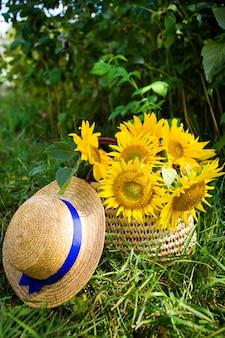 Kapelusz, bukiet słoneczników leży w torbie ze słomą na zielonej trawie.