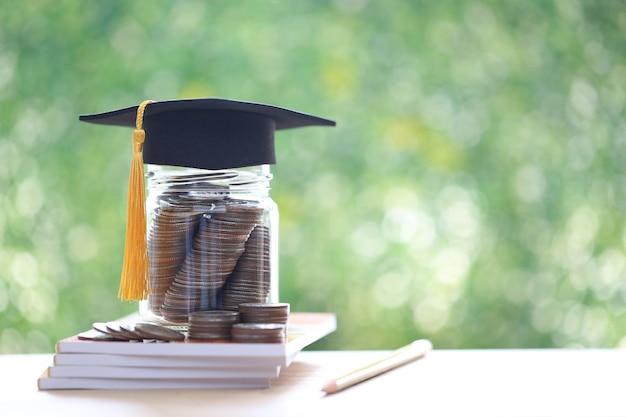 Kapelusz dyplomowy na monetach pieniądze w szklanej butelce na naturalnym zielonym tle