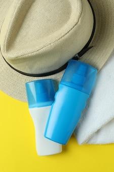 Kapelusz, filtry przeciwsłoneczne i ręcznik na żółto