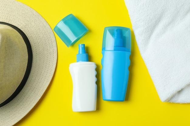 Kapelusz, filtry przeciwsłoneczne i ręcznik na żółtym tle na białym tle