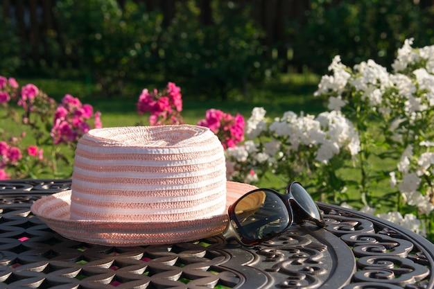 Kapelusz i okulary przeciwsłoneczne na stole w ogrodzie