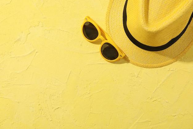 Kapelusz i okulary przeciwsłoneczne na żółtym, widok z góry