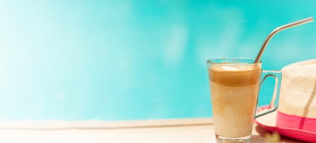 Kapelusz i zimna kawa frappe ze stalową słomką. witam letnie wakacje basen tło. koncepcja turystyczna. skopiuj miejsce