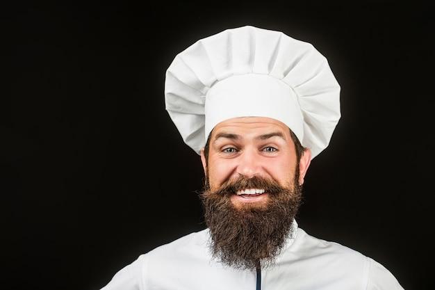 Kapelusz kucharski. brodaty szef kuchni, kucharz lub piekarz. brodaty mężczyzna szefów kuchni na czarnym tle.