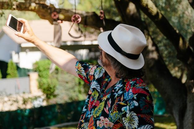 Kapelusz męski z koszulą w kwiatowy wzór, który robi selfie w ogrodzie