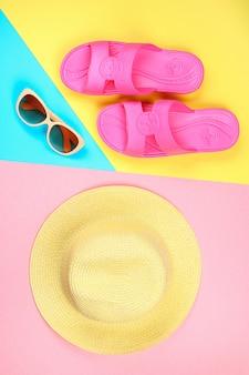 Kapelusz, okulary przeciwsłoneczne i kapcie na trójkolorowym pastelowym tle: niebieskim, żółtym i różowym.