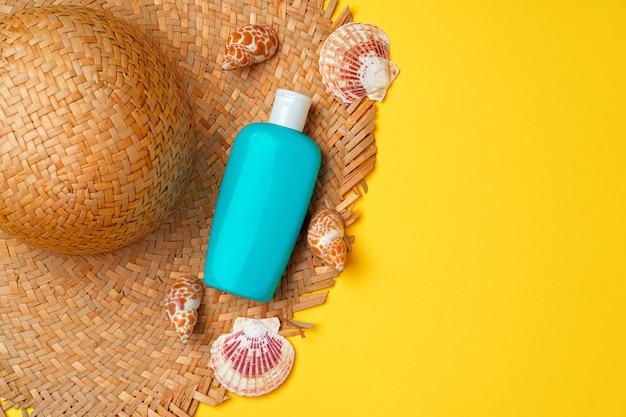 Kapelusz plażowy i butelka z filtrem przeciwsłonecznym, leżąca płasko