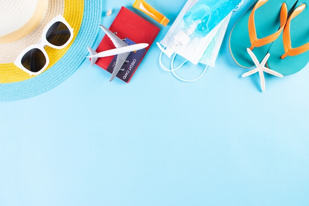 Kapelusz plażowy, okulary przeciwsłoneczne, maska ochronna, dezynfekcja rąk, paszport na jasnoniebieskim tle. lato.