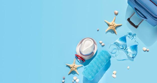 Kapelusz plażowy, walizka, okulary przeciwsłoneczne, ręcznik, rozgwiazda, muszle dla kobiet podróżujących w wakacje.