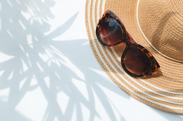 Kapelusz przeciwsłoneczny i okulary przeciwsłoneczne z cieniem drzewa palmowego