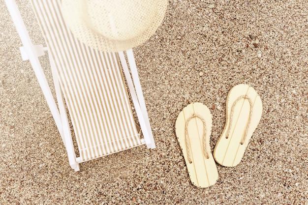 Kapelusz przeciwsłoneczny na leżaku i para klapek na piaszczystej plaży w jasnym słońcu. skopiuj miejsce wakacje.