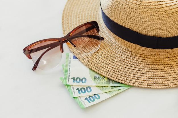 Kapelusz przeciwsłoneczny z okularami przeciwsłonecznymi i 100 setnymi banknotami euro. koncepcja wakacje