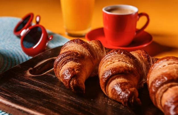 Kapelusz, rogalik przeciwsłoneczny z filiżanką kawy i szklanką soku pomarańczowego na żółtym stole w słońcu