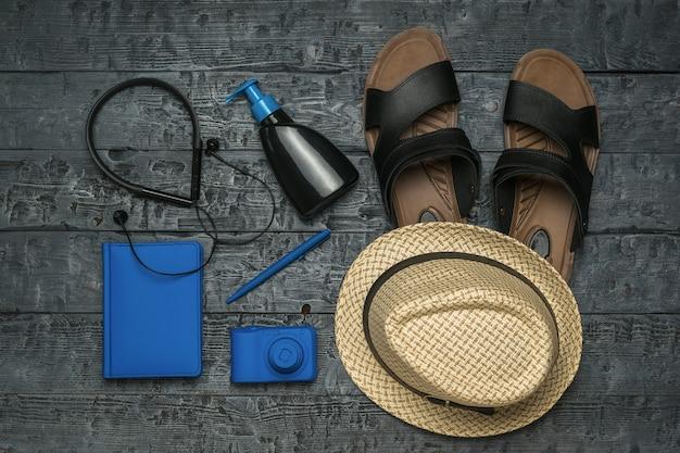Kapelusz, słuchawki, aparat i notatnik na drewnianym stole. pojęcie planowania podróży.