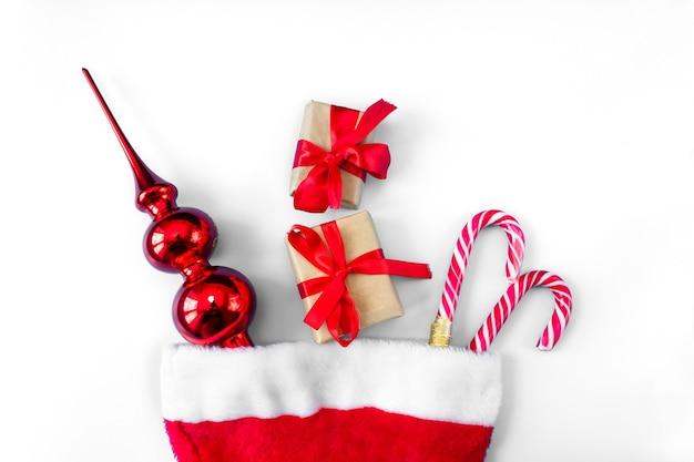 Kapelusz świętego mikołaja z karmelowymi sztabami, pudełkami na zabawki i prezenty na białym tle.