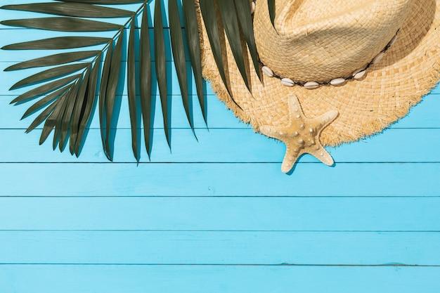 Kapelusz w kształcie liścia chico i rozgwiazda na jasnoniebieskim drewnianym tle z miejscem na kopię