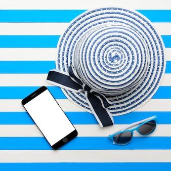 Kapelusz w paski, okulary przeciwsłoneczne i smartfon na białym i niebieskim tle. widok z góry, płaski układ.