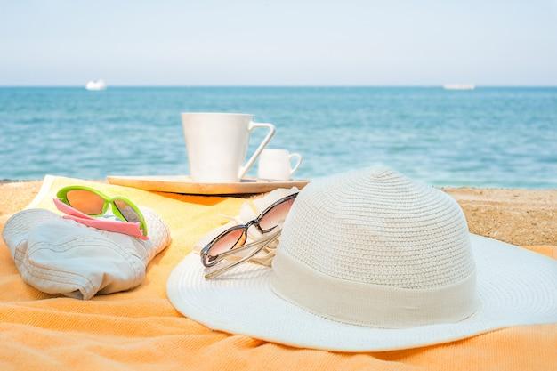Kapelusze na ręczniku na plaży. dziecięce i damskie kapelusze na pomarańczowy ręcznik z kubkiem na tle morza