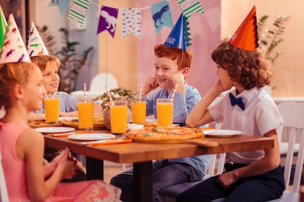 Kapelusze papierowe. pozytywnie zachwycony chłopak z uśmiechem na twarzy siedząc naprzeciw uroczych dziewczyn