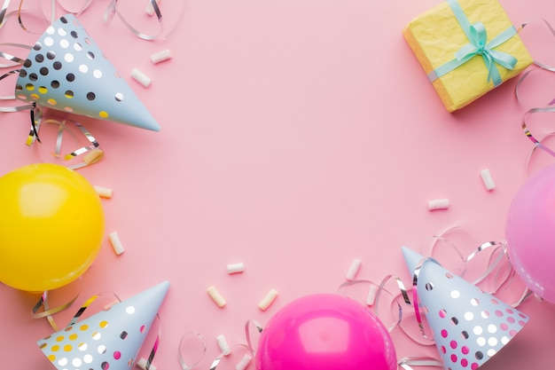 Kapelusze urodzinowe, różowe, żółte kulki, żółte pudełko i srebrna serpentyna na różowym tle. tło wakacje.